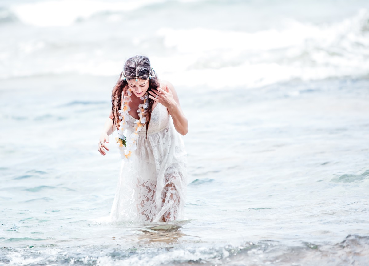 After stepping out of the ocean, the bride realizes that her trash-the-dress wedding gown is see-through.