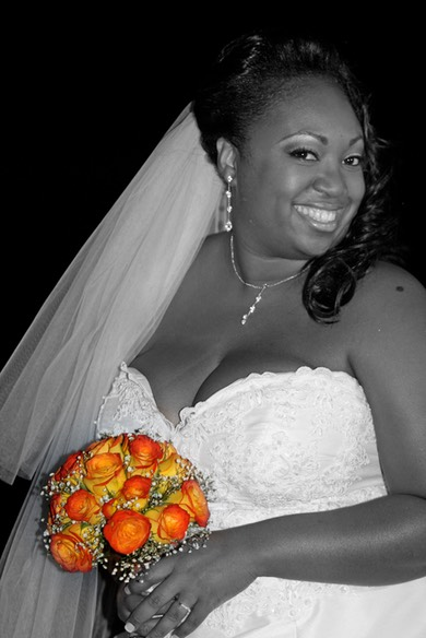 Black and white image of a bride holding flowers which are in color