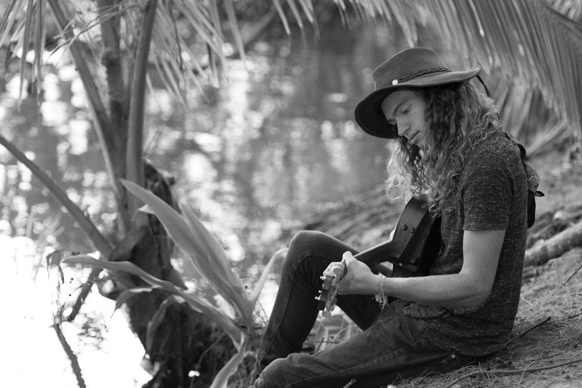 Kauai male model Steven Sedalia hanging by the river bank writing a song