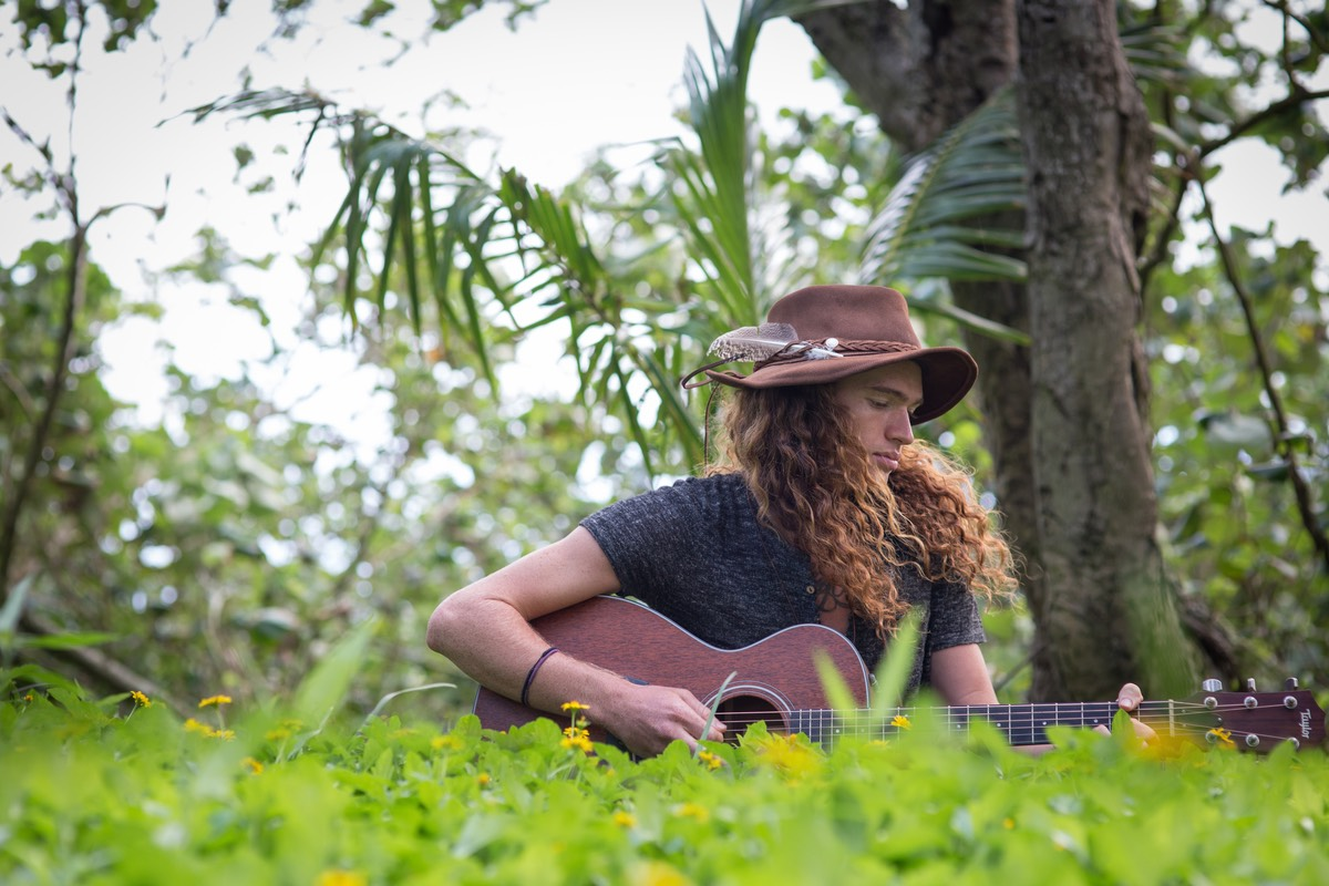 Kauai male model Steven Sedalia has the song figured out and settles down in the grass to play it.