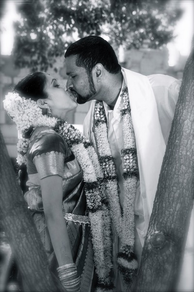 Young Indian couple share a kiss behind a tree after the wedding