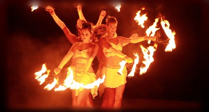 Nighttime image of female fire dancers in Kauai performing a fire dance.